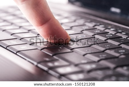 Using a laptop, finger on laptop keyboard - stock photo