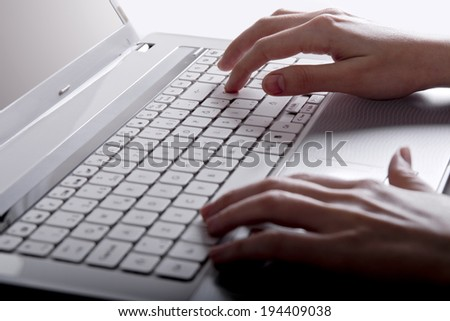 Using a laptop, finger on touch pad - stock photo