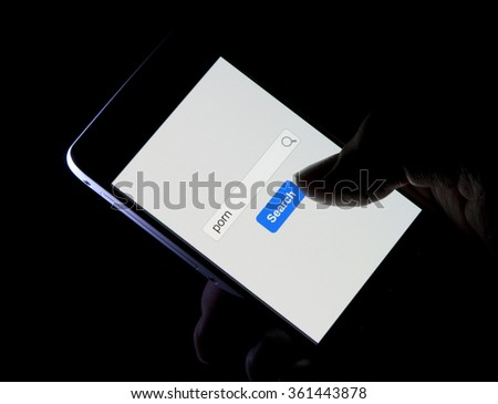 Using a mobile phone in the dark to search for pornography on the internet - stock photo
