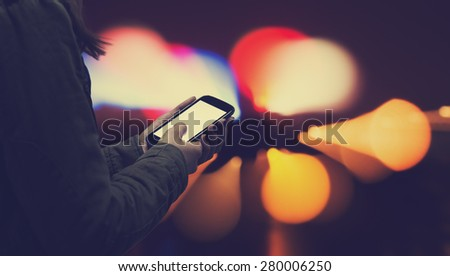 Using cellphone at night - with defocused city lights in the background. - stock photo