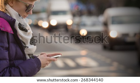 Using cellphone outdoors while crossing the street. Danger! - stock photo