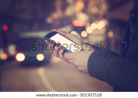 Using cellphone outdoors - with defocused city traffic. - stock photo