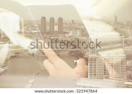 Using digital tablet double exposure and and cityscape background. Business & technology concept.  - stock photo