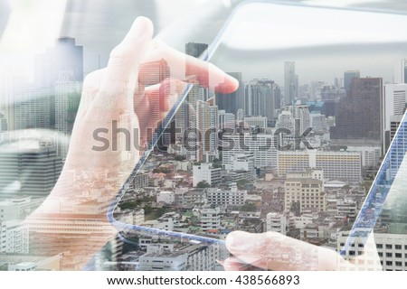 Using digital tablet double exposure and and cityscape background.Communication technology