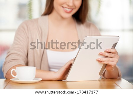 Using free Wi-Fi. Cropped image of beautiful young woman sitting at the restaurant and using digital tablet
