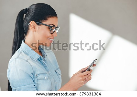Using her smart phone with pleasure. Close-up side view of beautiful young cheerful woman in glasses using her smart phone with smile while standing against grey background - stock photo