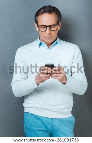 Using his phone for being in touch. Confident mature man holding mobile phone while standing against grey background - stock photo