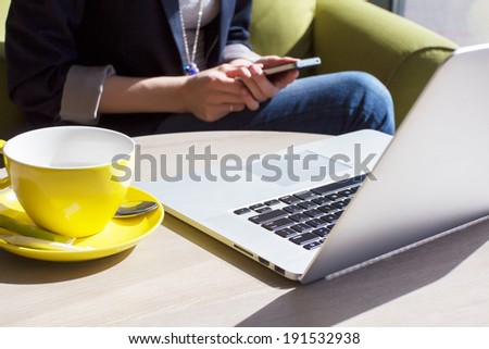 Using mobile phone and laptop computer in cafe - stock photo