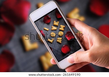 using mobile phone to take photos of Cookies ABC in the form of word I LOVE MOM alphabet with red rose petal on old jean background, Valentines day - stock photo