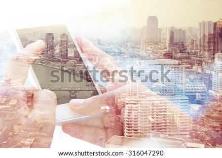 Using smart phone double exposure and bangkok cityscape in the background - stock photo