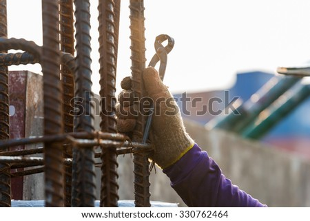 Using steel wire for securing steel bars with wire rod for reinforcement of concrete or cement. focus to activity work. - stock photo