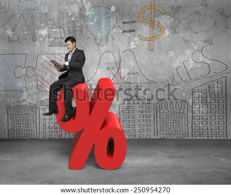 Using tablet businessman sitting on red percentage sign with business concept doodles wall background - stock photo