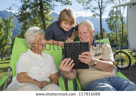 Using tablet computer and camping - stock photo