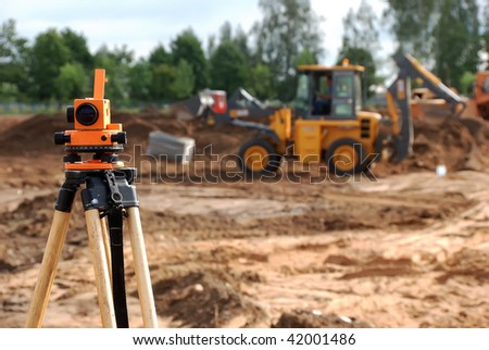 Using theodolite at construction site for land level measurement - stock photo