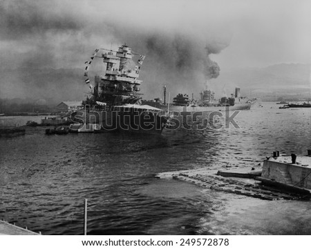USS California lists after aerial blows taken during the Japanese attack on Pearl Harbor. In distance the USS Neosho, cautiously backs away from berth, avoiding capsized USS Oklahoma. Dec. 7, 1941. - stock photo
