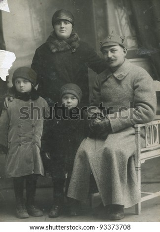 USSR - CIRCA 1927: A photo taking in the USSR, shows the family of the Red Army, a man, woman and two children, circa 1927