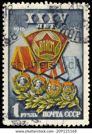 USSR - CIRCA 1953: A Stamp printed in the USSR shows the Komsomol badge against Lenin two awards, awards of the Red flag and an award of the Labour Red flag-awards of Komsomol, circa 1953 - stock photo
