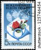 USSR - CIRCA 1989: A stamp printed in the USSR with a rose, envelope, postal horn, and globe commemorating International Letter Writing Week, circa 1989. - stock photo