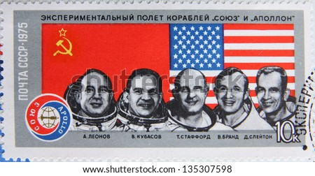 """USSR - CIRCA 1975: Post stamp printed in the USSR shows portraits of astronauts, experimental flight of the ships """"Union"""" and """"Apollo"""", circa 1975 - stock photo"""