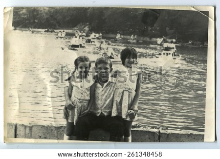 Ussr - CIRCA 1980s: An antique Black & White photo show boy and two girls sitting on the shore
