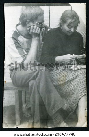 Ussr - CIRCA 1980s: An antique Black & White photo show man and woman sitting on a bench and reading letters