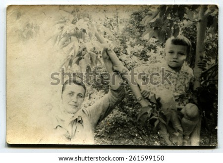 Ussr - CIRCA 1960s: An antique Black & White photo show mother with son in the garden