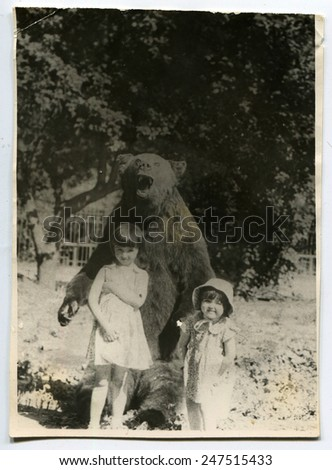 USSR - CIRCA 1980s: two little girls standing next to the bear, circa 1980s