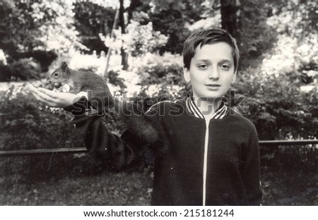 USSR - CIRCA 1975s : Vintage photo shows a boy feeding a squirrel.