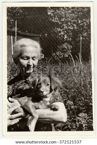 USSR - CIRCA 1980s: Vintage photo shows old woman cradles dog (dachshund).