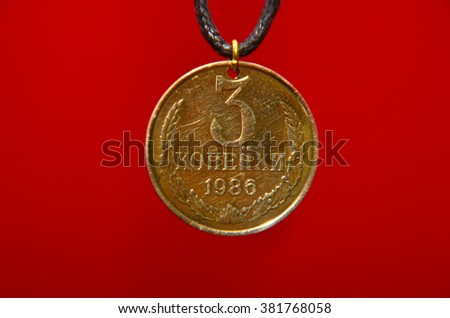 USSR Coin Necklace. Old coin of soviet copecks isolated over red background. Soviet Union. three kopeck of the Soviet Union. USSR Coin Necklace on red background - stock photo