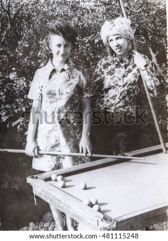USSR, LENINGRAD, GORELOVO - CIRCA 1973: Vintage photo of two young women playing Billiard