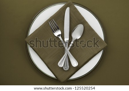 Utensils on plate with green table napkin and background - stock photo