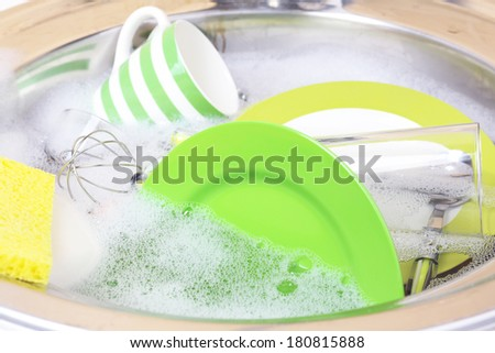 Utensils soaking in kitchen sink - stock photo