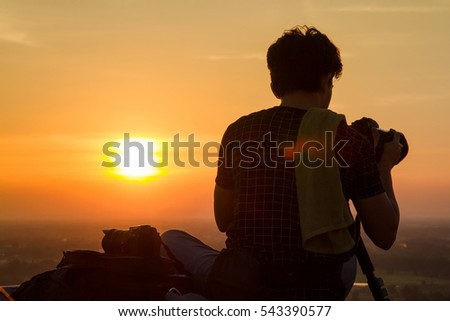Uthai Thani, Thailand - December, 17, 2016 : Silhouette of photographer taking pictures with camera in sunset sky at Wat Sangkat Rattana Khiri on Khao Sakae Krang mountain in Uthai Thani, Thailand