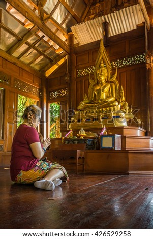 UTHAI THANI, THAILAND - MAY 22, 2016: Worship Perspective in Thai Buddhism. Asian woman worships the Buddha statue in Buddhist temple.