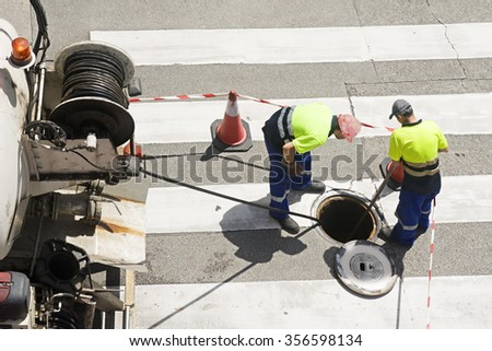 utilities workers moves the manhole cover to check the sewer line for clogs - stock photo