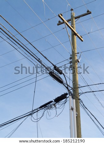 Utility pole hung with confusing and messed-up electricity power cables and telephone lines for residential supply - stock photo