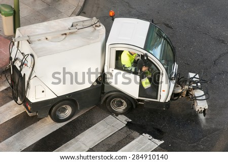 utility service company men workers with street sweepers electrical vehicles cleaning the street at city  - stock photo