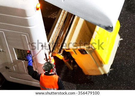 utility service company worker man for cleaning the dumpsters containers of city street in the night in motion blur - stock photo