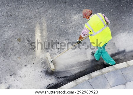 utility service worker sweeping up on rough concrete in city street  using a large broom - stock photo