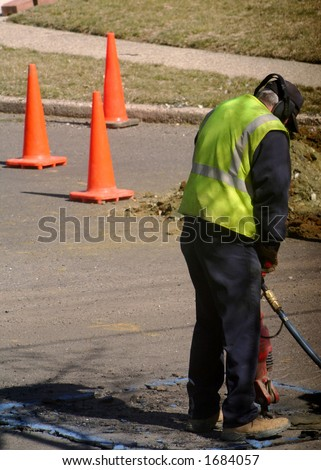 Utility worker using a jackhammer. - stock photo