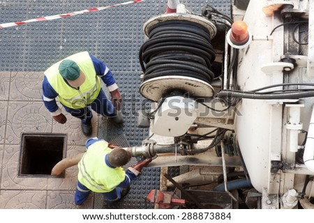 utility  workers moves the manhole cover to cleaning the sewer line for clogs - stock photo