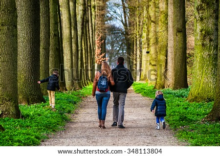 UTRECHT, NETHERLANDS - MARCH 15, 2014: Family walking down the pathway at beautiful garden of De Haar Castle in spring. The park is designed by Hendrik Copijn and has many waterworks and gardens. - stock photo