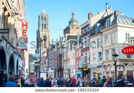 UTRECHT, NETHERLANDS - MARCH 03, 2014:: People walking on the old town street, in front of the Dom Tower. Cathedral (Dom) tower is the symbol of the city and the tallest church tower in Netherlands.  - stock photo