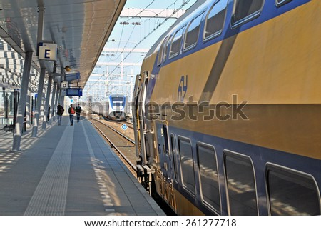 UTRECHT, THE NETHERLANDS, 13 March 2015 - Yellow train of the Dutch railway company Nationale Spoorwegen (NS) arriving at platform.