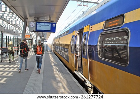 UTRECHT, THE NETHERLANDS, 13 March 2015 - Yellow train of the Dutch railway company Nationale Spoorwegen (NS) arriving at platform. - stock photo