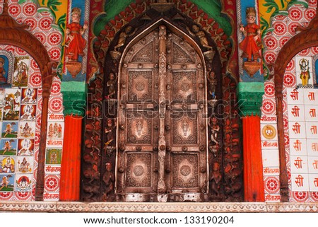 UTTAR PRADESH, INDIA - JAN 27: Beautiful metal doors of the Hanuman temple framed by colorful figures, patterns and drawings on January 27 2013 in Ayodhya India. Uttar Pradesh state covers 243,290 km2 - stock photo