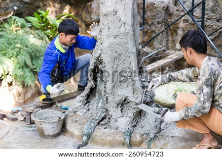 Uttaradit, Thailand - December 19, 2014: The workers are grouting cement on the fake tree trunk in Lomyen shop.