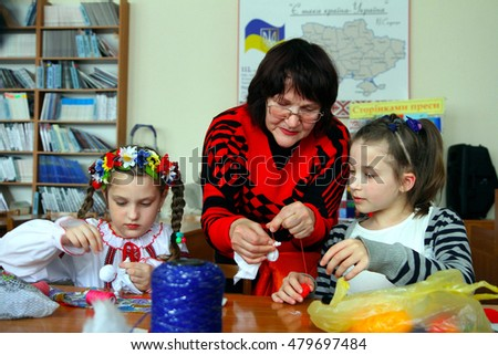 Uzhhorod, Ukraine - March 21. 2016: An older woman teaches girls to make soft toys and handmade souvenirs during the master class.