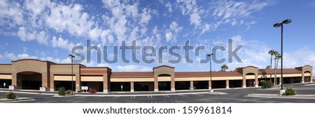 Vacant business offices and shopping mall with empty parking lot for rent - stock photo